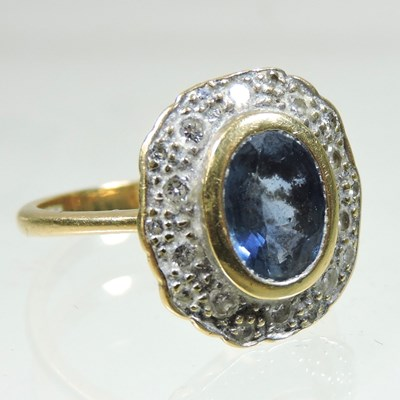 Lot 24 - An 18 carat gold sapphire and diamond cluster ring